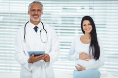 Doctor and pregnant woman smiling at camera Stock Photography
