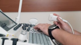 The doctor prepares equipment for ultrasound. Hands of the specialist close-up. The man presses the buttons of the. Ultrasound unit and takes in the transducer` stock video
