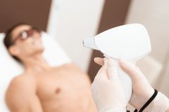 The doctor is preparing a laser hair removal machine. Against the background is the man who will be given procedure. The doctor is preparing a laser hair stock image