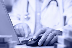 Doctor preparing online internet medical record. Blue tone royalty free stock photo