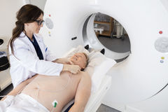 Doctor Preparing Patient For CT Scan In Hospital Stock Image