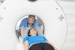 Doctor Preparing Patient For CT Scan In Hospital. Smiling male doctor preparing female patient for CT scan in hospital Stock Images