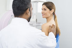 Doctor Preparing Patient For Mammogram Test. Rear view of male doctor preparing female patient for mammogram x-ray test in hospital Stock Images