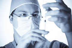 Doctor preparing a syringe i Stock Photos