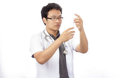 Doctor preparing a syringe on a white background Stock Photos