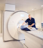 Doctor Preparing Woman For MRI Scan In Laboratory Royalty Free Stock Images