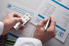 Doctor prescribing drugs and showing blood test report top view. Doctor prescribing drugs and showing blood test report with documents and medicines on a white stock photos