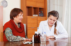 Doctor prescribing medication to senior woman Stock Photos