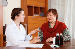 Doctor prescribing medication to  woman Royalty Free Stock Photos