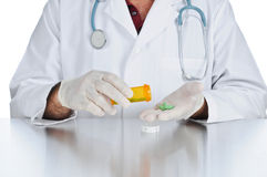 Doctor prescribing medicine. Doctor counts tablets in a prescription Royalty Free Stock Photography