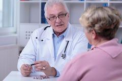 Doctor prescribing medicines. Older doctor prescribing to aged female patient medicines Royalty Free Stock Photos