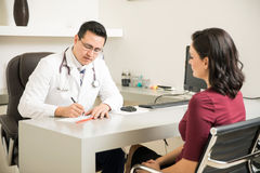 Doctor prescribing some medicine to patient. Handsome doctor prescribing some medicine to a patient in his office royalty free stock photo
