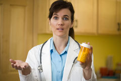 Doctor with prescription bottle. Woman doctor explaining prescription medication to the camera Royalty Free Stock Photo