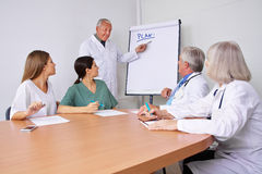 Doctor in a presentation explaining plan Royalty Free Stock Photos