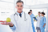 Doctor presenting an apple in his hand. In front of his medical team Royalty Free Stock Photography