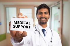Doctor presenting medical support text on card. Friendly indian doctor man presenting medical support black text on white business card stock photo