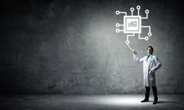 Doctor and processor icon. Confident and young doctor in white medical uniform standing against dark gray wall on background and interracting with glowing stock images