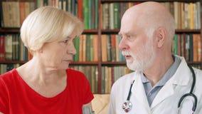 Doctor profesional de sexo masculino en el trabajo Médico mayor que consulta al paciente enfermo en casa sobre el tratamiento almacen de metraje de vídeo