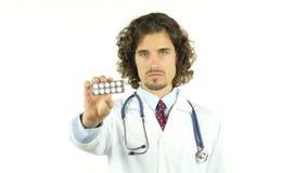 Doctor profesional que muestra píldoras de la medicación almacen de video