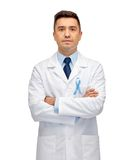 Doctor with prostate cancer awareness ribbon Royalty Free Stock Photography