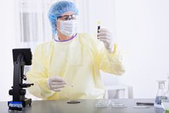 Doctor in protective gear holding blood sample Stock Photography