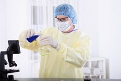 Doctor in protective gear holding blood sample Royalty Free Stock Images
