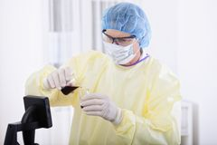 Doctor in protective gear holding blood sample. Portrait of scientist or doctor in protective gear working with microscope and blood, in lab or hospital Stock Image