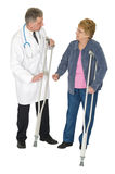 Doctor Patient Senior Woman, Crutches, Isolated. A doctor provides healthcare and treatment for a mature senior women who needs a medical device or crutches to Royalty Free Stock Photography