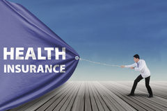 Doctor pulling a health insurance banner Royalty Free Stock Photography