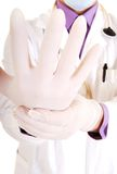Doctor pulling on surgical glove. Royalty Free Stock Photos