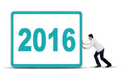 Doctor pushing billboard with number 2016. Image of a male young doctor pushing billboard with number 2016 in the studio Royalty Free Stock Photography