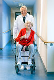 Doctor pushing an elderly woman in a wheelchair. Royalty Free Stock Image