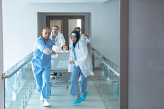 Doctor pushing emergency stretcher bed in corridor at hospital royalty free stock photography