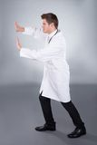 Doctor Pushing Invisible Wall Royalty Free Stock Image