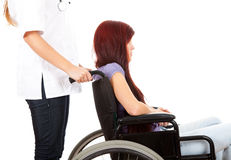 Doctor pushing patient on a wheelchair Stock Photo