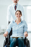Doctor pushing a patient in wheelchair Stock Images