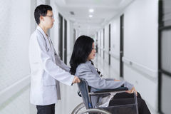 Doctor pushing patient with wheelchair in hospital Royalty Free Stock Images