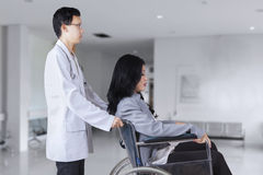 Doctor pushing patient on wheelchair Stock Image