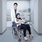 Doctor pushing patient with wheelchair Royalty Free Stock Photo