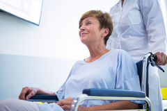 Doctor pushing senior patient on wheelchair Stock Images