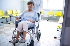 Doctor pushing senior patient on wheelchair Stock Photos