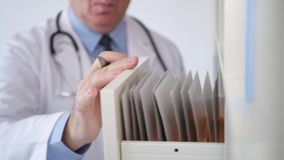 Doctor put back in hospital archive a medical record and close the drawer.  stock video footage