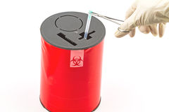 Doctor put needle in red disposal boxes on white background. Doctor put needle in red disposal boxes Royalty Free Stock Photos
