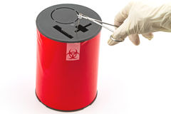 Doctor put needle in red disposal boxes on white background Royalty Free Stock Image