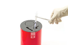 Doctor put syringe in red disposal boxes on white background royalty free stock photo