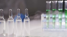 Doctor puts ampoules with medicine on the table. Concept - vaccination, modern medicines, development of new drugs