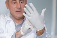 Doctor puts glove on hand. Doctor puts a glove on his hand Stock Photography