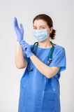 Doctor putting on blue surgical gloves Stock Image