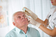 Doctor putting drops into a senior man's eyes Stock Images