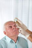 Doctor putting drops into a senior man's eyes Royalty Free Stock Photo